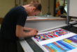 Daryl Berrecloth checks print quality as the Swarez Collection wall calendar comes